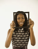 Young woman holding a frame before her face — Stock Photo