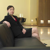 Asian businesswoman sitting in lobby — Stock Photo