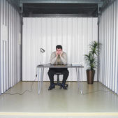 Businessman sitting at desk in storage unit — 图库照片