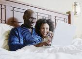 Par shopping online i sängen — Stockfoto