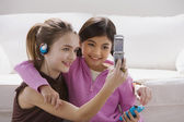 Two girls taking their own photograph with cell phone — Stock Photo