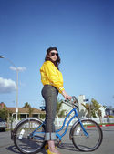 Woman standing over bicycle — Photo