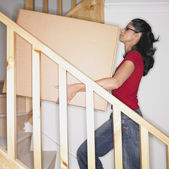 Woman carrying box up stairs in new house — Stock fotografie