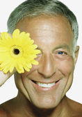 Mature man holding a sunflower by his face — Stock Photo