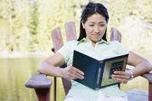 Mujer sentada en la cubierta por lectura de lago — Foto de Stock