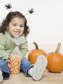 Portrait of little girl with pumpkins and candy corn — Stock Photo