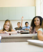 Students smiling at desks in classroom — Stock Photo