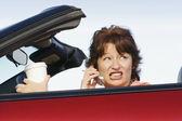 强调女人开车用手机谈话时可转换 — 图库照片