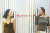 Two female friends standing by recycling sign — Stock Photo