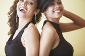 Two African American women back to back smiling — Stock Photo