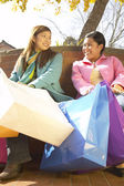 Two women sitting with shopping bags outdoors — Stock Photo