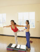 Exercise trainer helping young woman stretch — Stock Photo