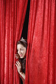 Hispanic beauty queen peeking through curtains — Stock Photo