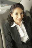 Businesswoman n the backseat of a car — Stock Photo