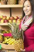 Asian woman holding pineapple in grocery store — Stock Photo