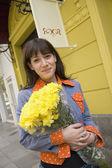 Hispanic woman with flowers on sidewalk — Stock Photo
