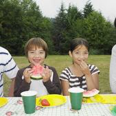 Mixed Race brother and sister eating watermelon — Stock Photo