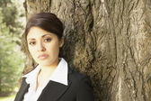 Hispanic businesswoman leaning on tree — Stock Photo