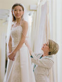 Young bride being fitted in her dress — Stock Photo