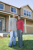 African couple posing in front of house — Stock Photo