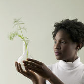 Woman holding plant in vase — Stock Photo
