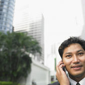 Businessman talking on cell phone outdoors — Stock Photo