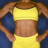 Young woman bodybuilder displaying defined muscles — Stock Photo