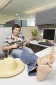 Hispanic businessman dressed casually playing a ukulele at his desk — Stock Photo