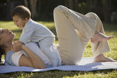 Baby sitting on mother outdoors — Stock Photo