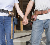 Couple holding hands and wearing tool belts — Stock Photo