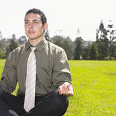 Businessman meditating in park — Stock Photo