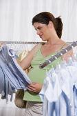 Mujer embarazada de las compras de ropa de bebé — Foto de Stock