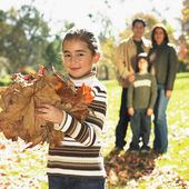 Mixed Race girl playing in autumn leaves — Stock Photo