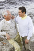 Hispanic father and adult son smiling at each other — Foto Stock