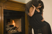Pregnant couple in fancy clothing hugging next to fireplace — Stock Photo