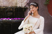 Hispanic girl on cell phone in Quinceanera dress — Stock Photo
