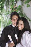 Homem e mulher segurando diplomas de faculdade — Fotografia Stock