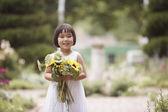 Girl in garden holding flowers — Stock Photo