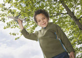 Boy standing outside with toy plane — Stock Photo
