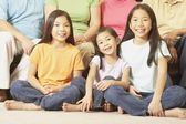 Three young Asian sisters sitting cross-legged on the floor — Stock Photo