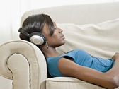 African woman laying of sofa listening to headphones — Stock Photo
