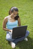 Hispanic girl typing on laptop — Stock Photo