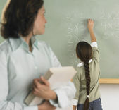 Student solving arithmetic on the chalkboard — Stock Photo