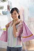 Chinese woman holding shopping bags — Stock Photo