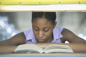 Teenage girl sitting in a library reading a book — Stock Photo