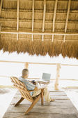 Young man using a laptop underneath thatch roof on the beach — 图库照片