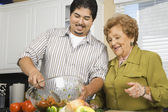 Hispanic mother and adult son preparing food in kitchen — Stock Photo