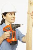 Hispanic female construction worker using drill — Stock Photo