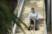带笔记本电脑坐在台阶上的商人 — 图库照片