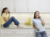 Two teenage girls talking on cell phones — Stock Photo